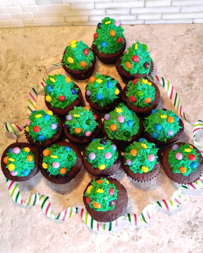 Arrange the Christmas tree cupcakes in the shape of a tree