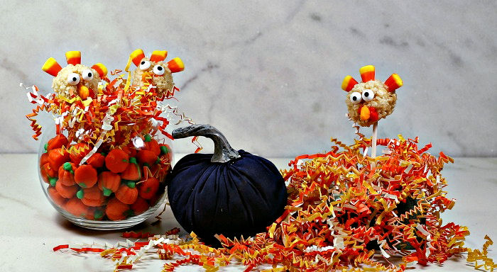 Rice Krispie turkey pops in a Thanksgiving display with shredded paper and candy pumpkins.