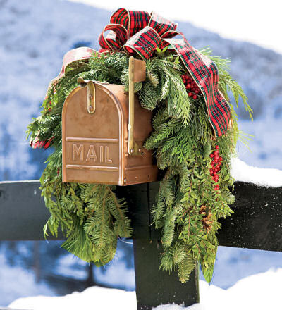 Rustic swag with red plaid ribbon trims this tan colored mail box beautifully