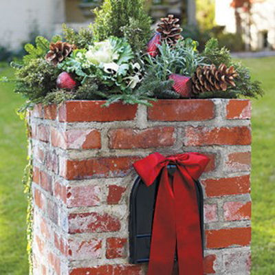 Large brick mailbox with a natural pine cone and fir topper