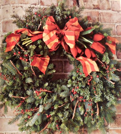 This wreath uses tulips instead of poinsettias as the focal point