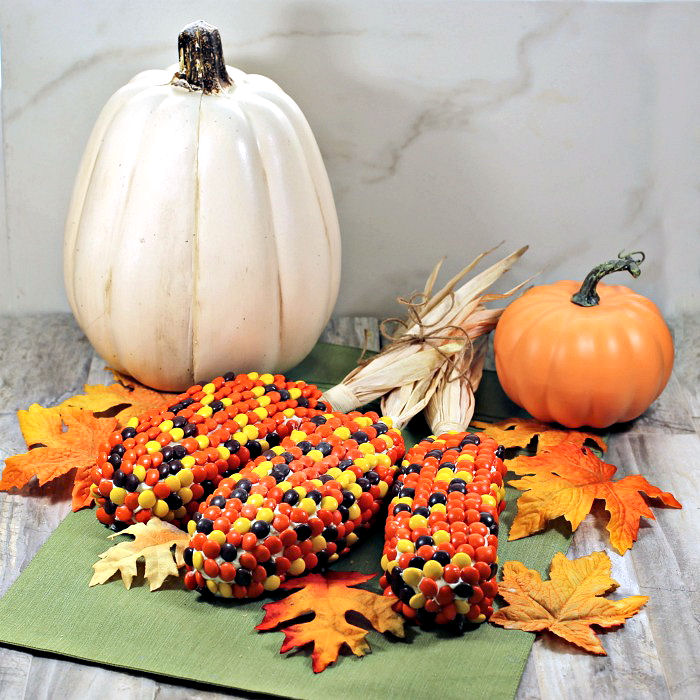 Thanksgiving centerpiece with pumpkins, leaves and ears of edible Indian corn.
