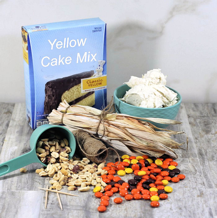 Yellow cake mix, frosting, Reese's pieces, peanuts, frosting, corn stalks, jute and toothpicks.