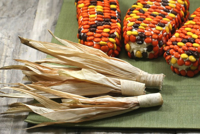 Corn husks wrapped next to cake slices with Reese's pieces.