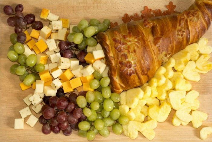Edible cornucopia filled with fruit and cheese.