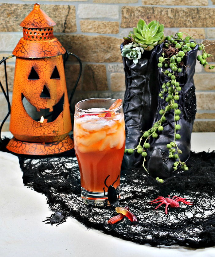 Witch shoes and pumpkin with an orange Halloween drink.