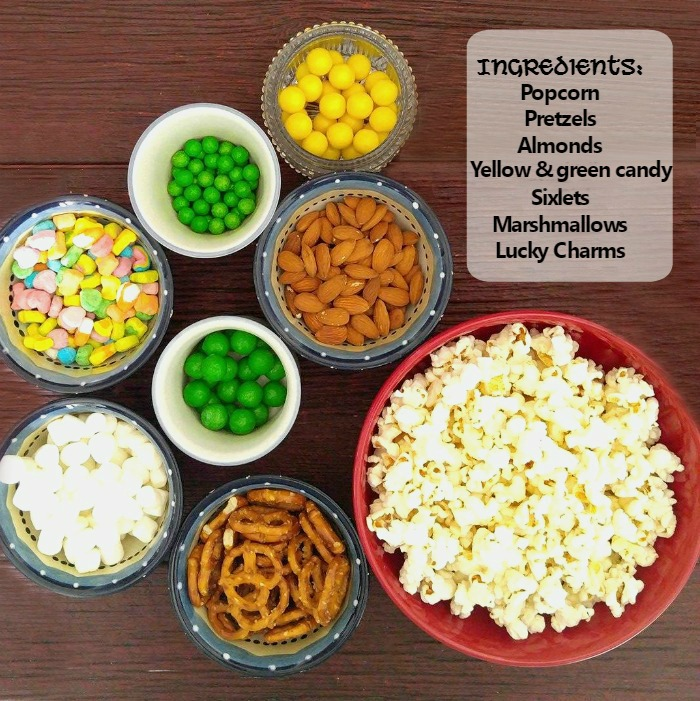 Bowls of snack foods with overlay reading Ingredients: popcorn, pretzels, almonds, yellow and green candy sixlets, marshmallows, Lucky Charms.