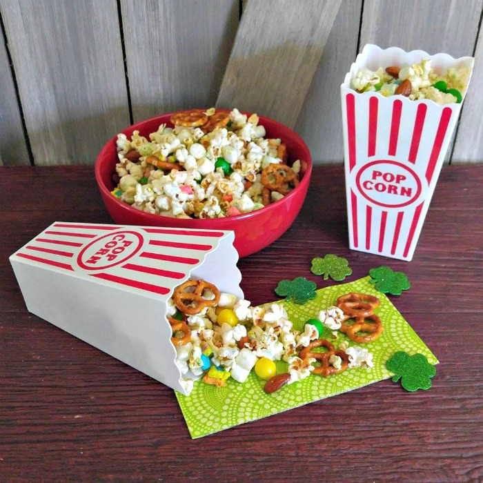 Bowl and popcorn containers with a snack mix containing popcorn, candy and pretzels.