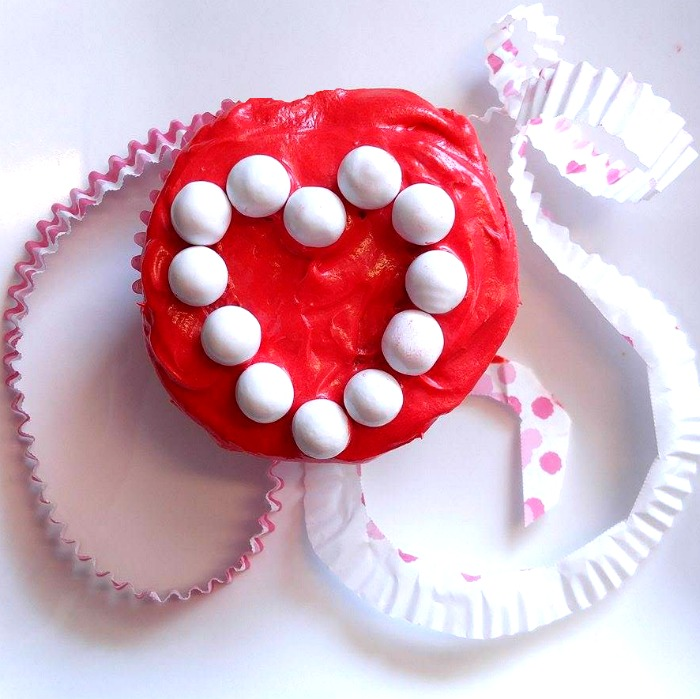 White sixlets make a heart shape on this Valentine Cupcake