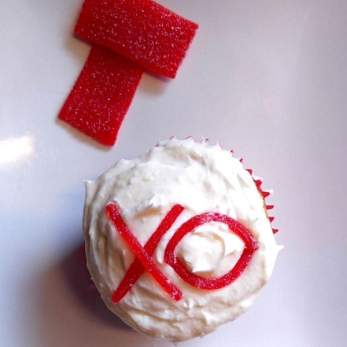 Decorating cupcakes with an XO on a Valentine Cupcake