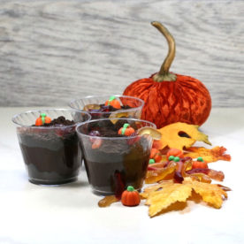 Dirt pudding dessert cups with leaves, worms and pumpkins.