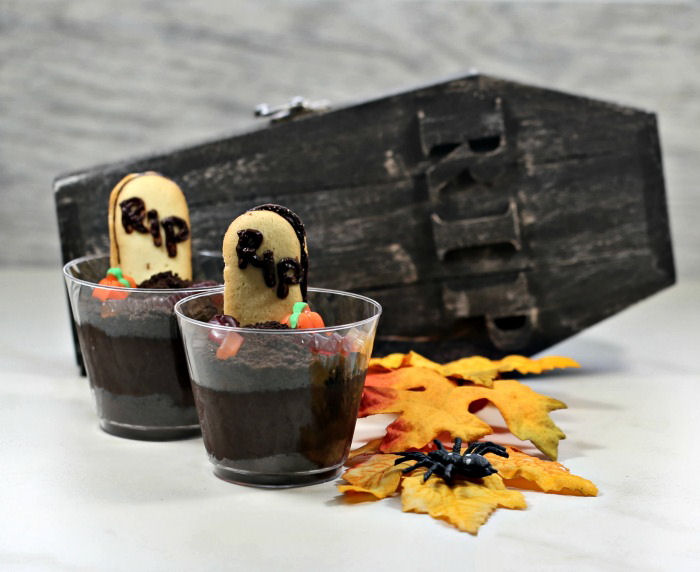 Dirt cups with RIP cookies, leaves and a wood coffin.