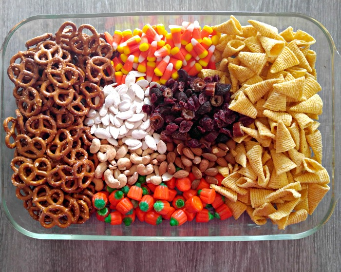 Glass bowl with pretzels, candy corn and pumpkins, Bugles snacks, nuts, pumpkin seeds and dried fruit.