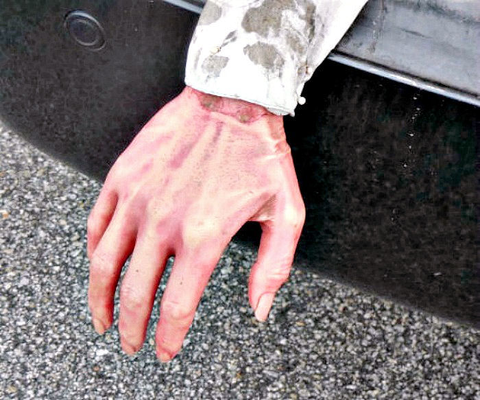 Fake hand sticking out the back of a car trunk.