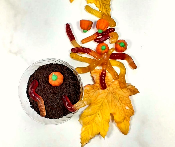 Gummy worms and candy pumpkin on a dirt pudding cup