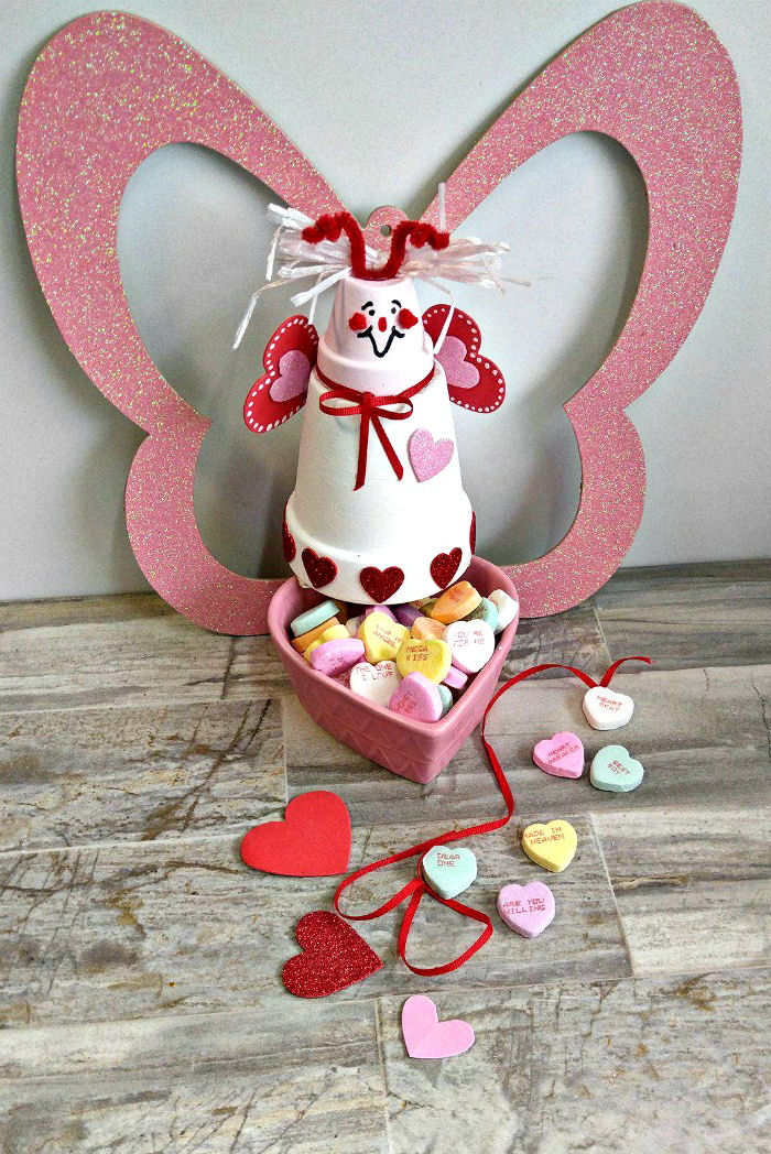 This Clay pot love bug candy dish is the perfect way to display conversation hearts. It is easy to make and takes about a hour to make. #lovebug #conversationhearts