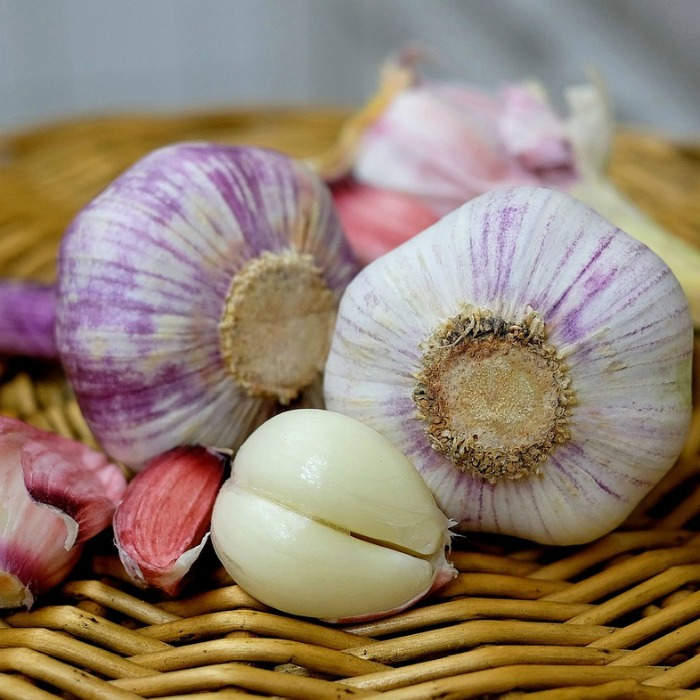 A clove of garlic, and three garlic bulbs on a wooden mat for National Garlic Day.