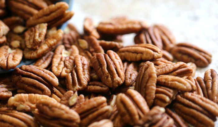 A pile of pecan nuts spilling onto a counter.