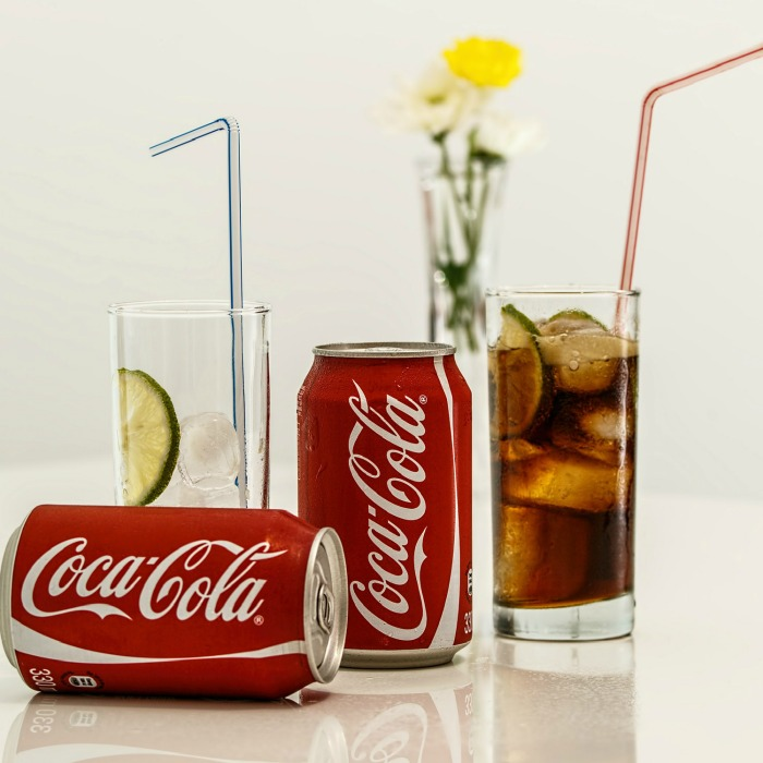 A glass of ice, and a glass of ice filled with Coke next to two Coca Cola cans.