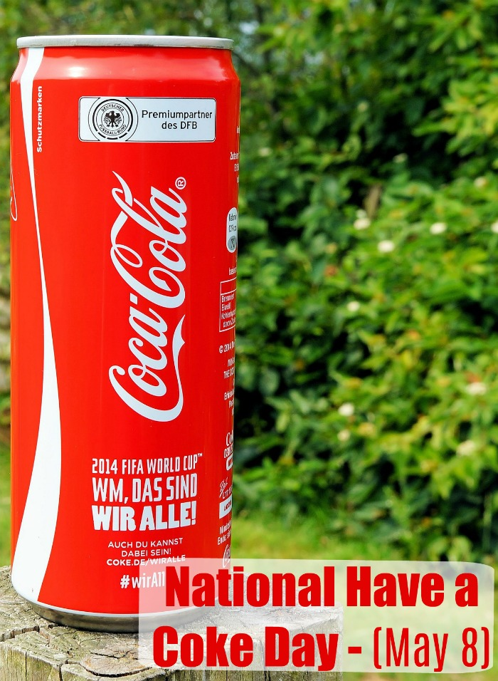"A tall Coke can on a wooden post in front of a hedge wit a text overlay reading ""National Have a Coke Day- May 8""."