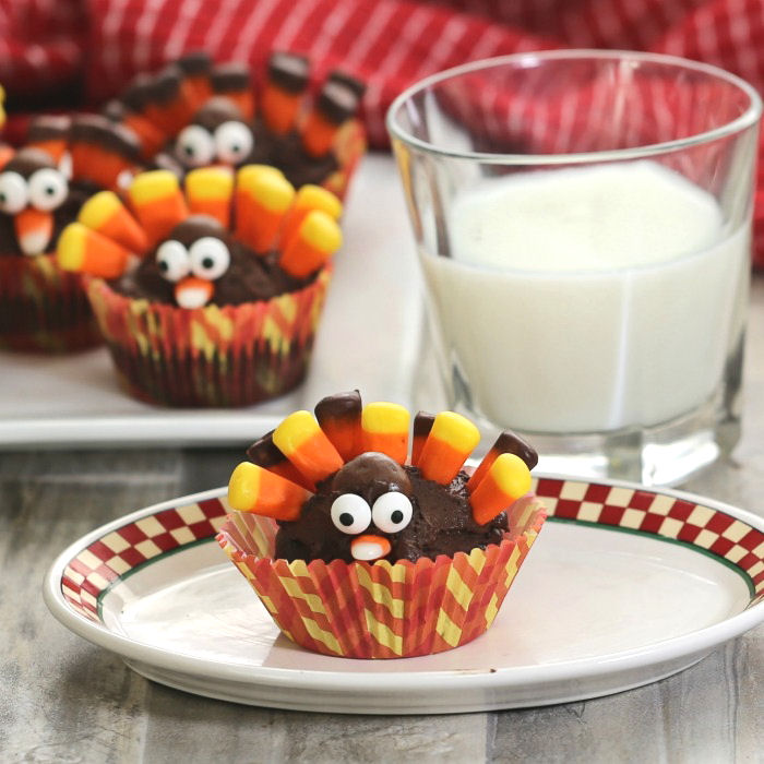 Cute turkey cupcakes and a glass of milk on white plates