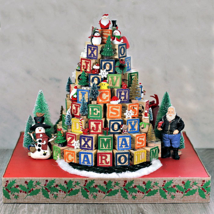 ABC block Christmas tree on a red base with miniatures and trees.