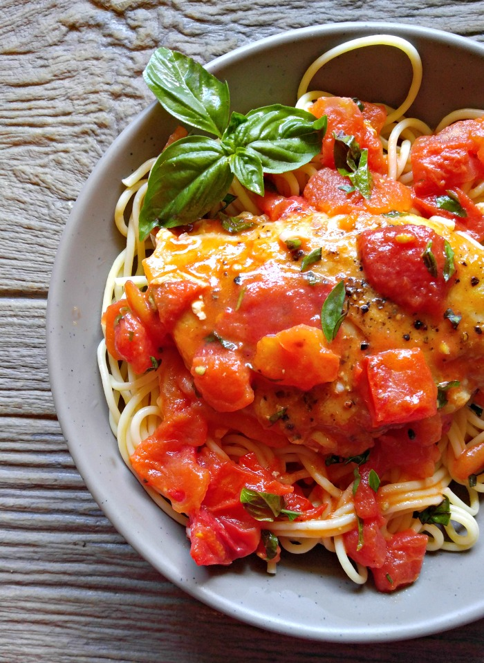 Buttery garlic chicken in a tomato sauce over spaghetti
