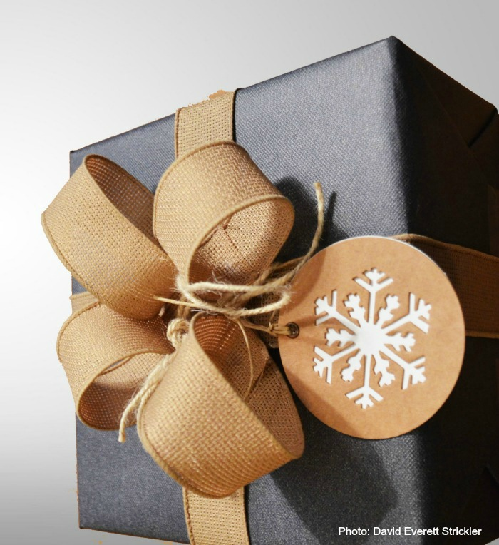 Blue wrapping paper with burlap ribbon and snowflake gift tag.