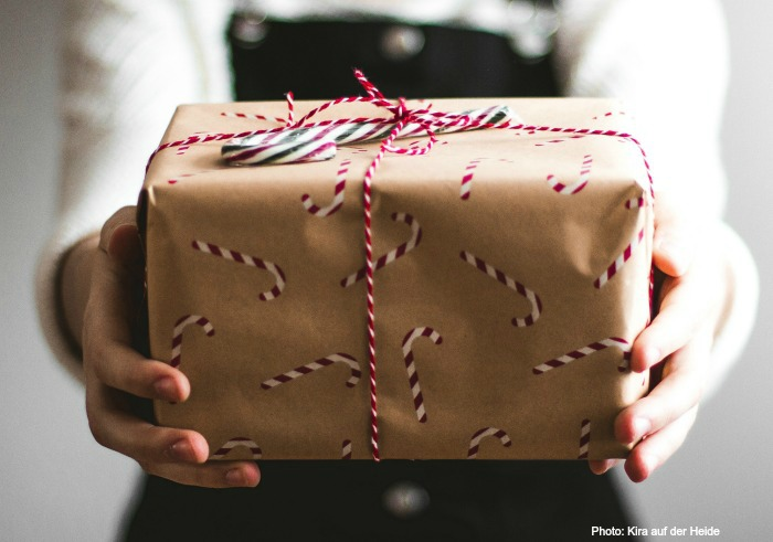 Gift holding package wrapped in butcher paper, kitchen twine and candy cane stickers.