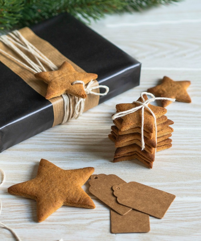 Christmas cookies on a blue gray Christmas gift and paper tags.