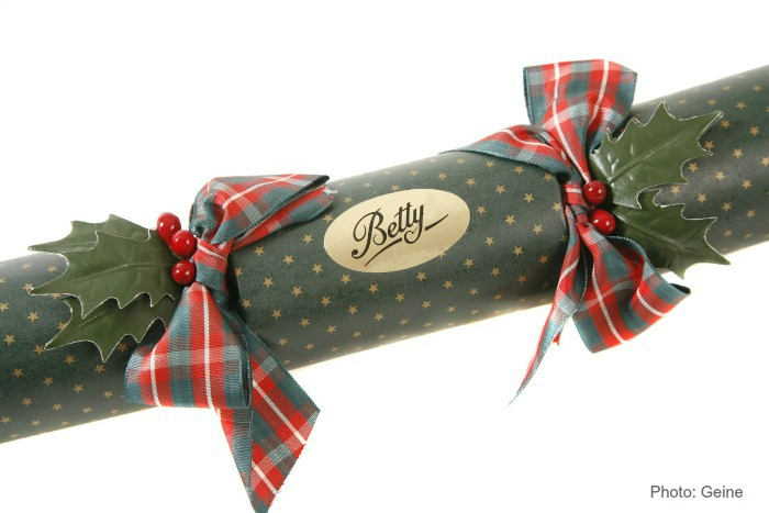 Cardboard tube wrapped with green paper, braided ribbon and personalized gold sticker.