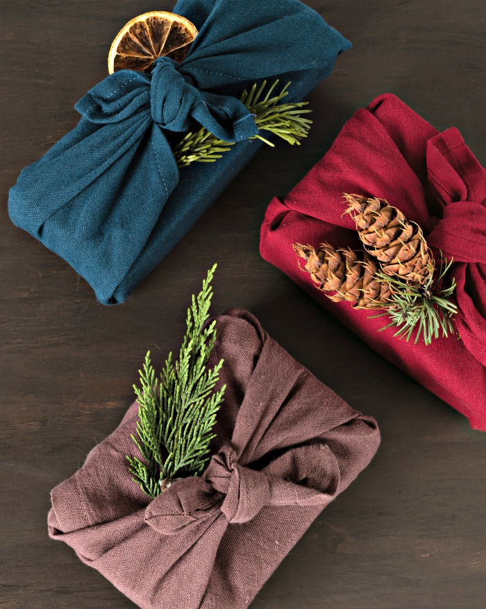 Furoshiki gifts. Eco friendly alternative green Xmas presents wrapped in clothes with boughs, pine cones and dried orange slices.