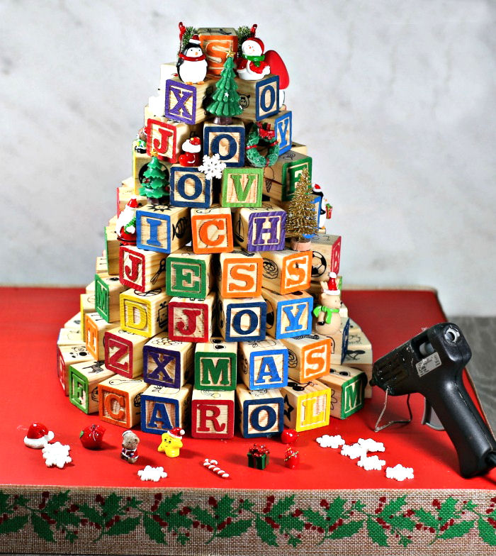 alphabet block tree with glue gun and mini ornaments on a red base.