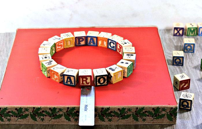 Ruler, alphabet blocks on Christmas base.