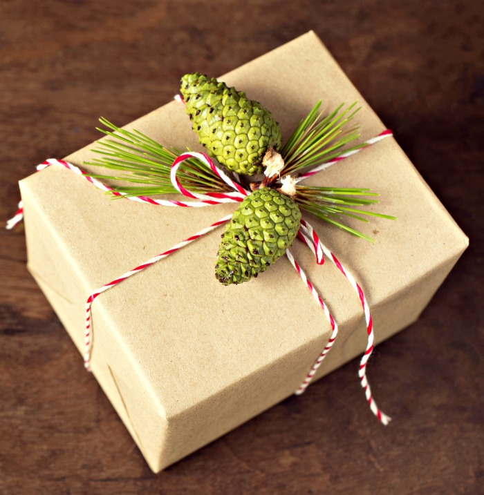 Christmas gift wrap with pine boughs and green pine cones tied with kitchen twine.