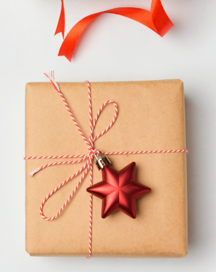 Christmas wrapping idea with butcher paper,. kitchen string and star ornament.