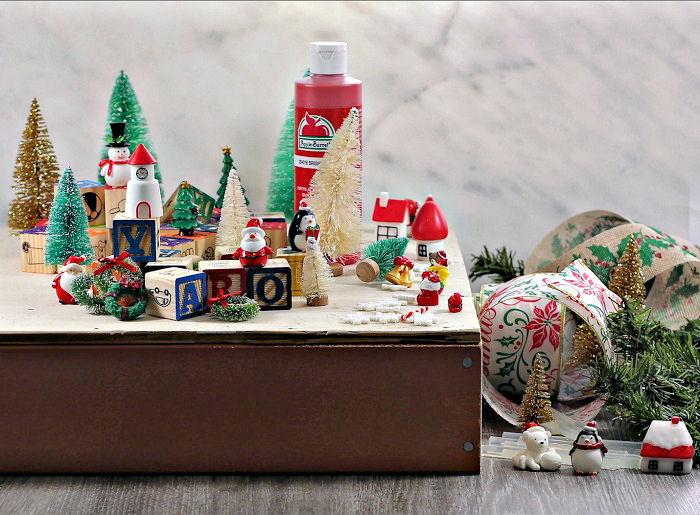 Paint, toys, blocks, ribbon and greenery for thealphabet blocks Christmas tree.