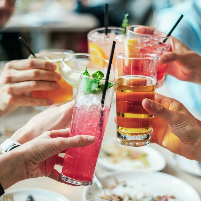 A group of five friends clinking cocktails over a brunch table.