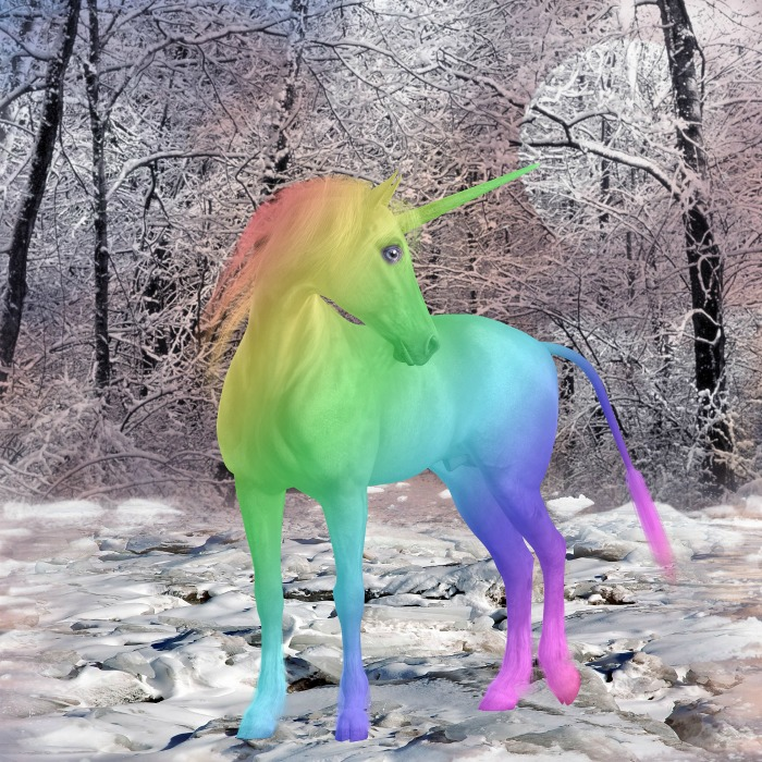 A rainbow unicorn standing in a forest covered in snow.