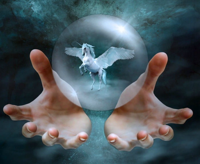 Two hands holding a clear glass ball with a flying unicorn inside.