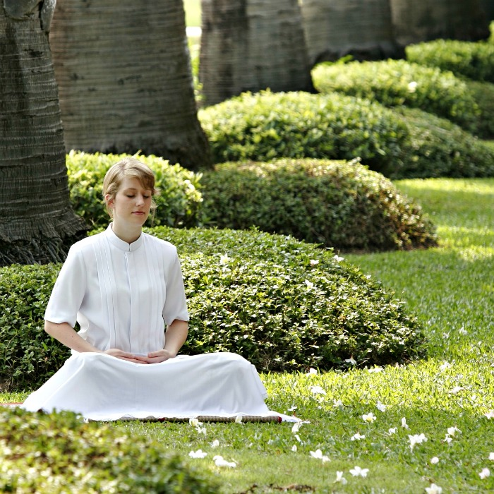 Woman in a white dress doing a seated meditation in a garden.