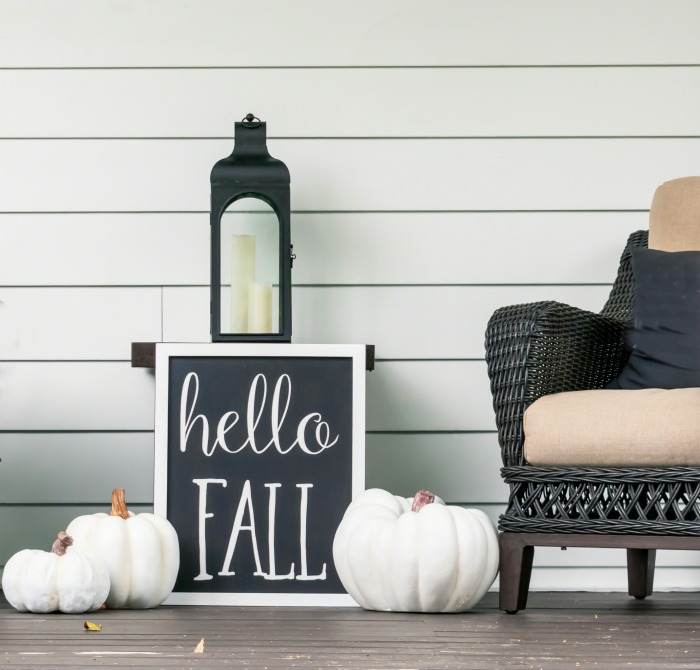 "Halloween porch decor with white pumpkins, chair, lantern and a sign that says ""hello fall."""