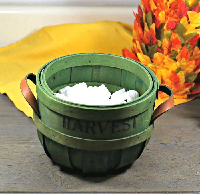 Harvest basket with packing peanuts near a yellow napkin and leaf tree.