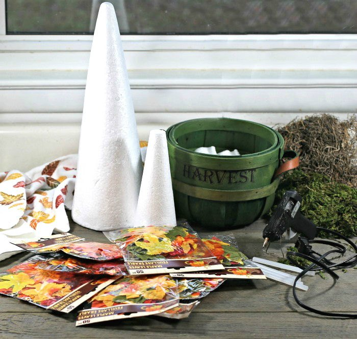 Foam cones, basket, moss, seeds, glue gun and fall towel.