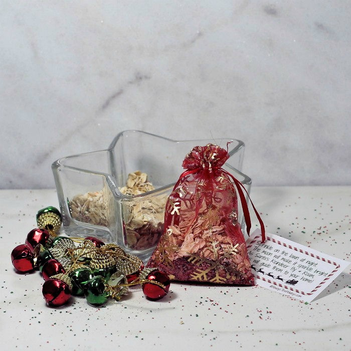 Red organza bag with oats and sugar near a star shaped dish and jingle bells.