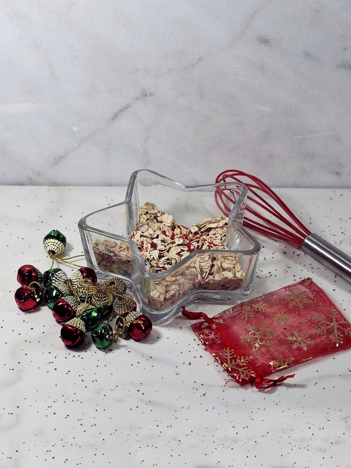 Rolled oats, sugar and sugar crystals in a glass star shaped bowl with whisk and red organza bag.