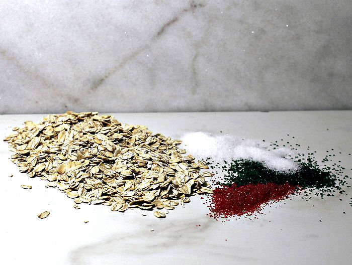 Rolled oats, granulated sugar, and sugar crystals on a countertop.
