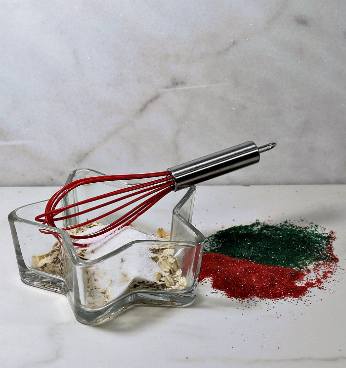 Rolled oats and sugar with whish in a star shaped bowl, with red and green sugar crystals on a counter.