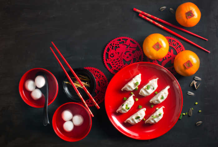 Food on red plates with chopsticks for Chinese New Year.