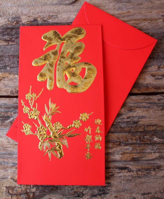 Gold and red money envelope on a wood board.
